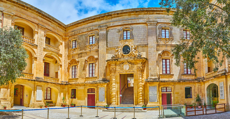 MDINA, MALTA - JUNE 16, 2018: Panorama of Magisterial (Vilhena) Palace from its courtyard wih a view on main entrance and carved stone decors, on June 16 in Mdina.