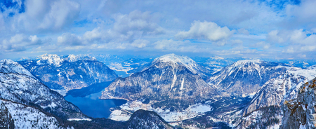 Panorama of Inner Salzkammergut landscape with snowy Alpine peaks of Dachstein and curved Hallstattersee lake in valley, Austria.