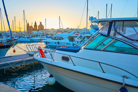 The view from marina on the silhouettes of yachts sails and Msida Parish Church in last sunset rays, Malta.