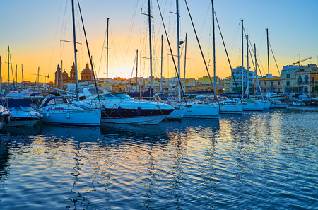 Enjoy the evening in harbour of Msida with a view on bobbing yachts, small boats and the Parish Church of St Joseph, hiding the setting sun, Malta.