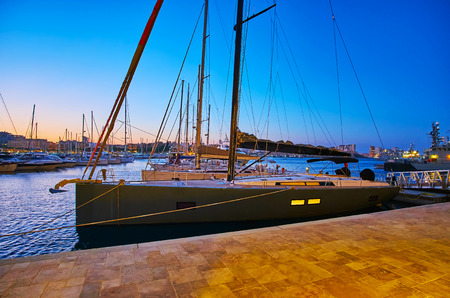 The pleasant evening walk along the shore of Valletta marina with a view on modern yachts, moored along the shipyards, Malta. Archivio Fotografico