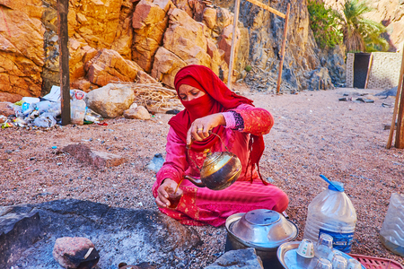 DAHAB, EGYPT - DECEMBER 16, 2017: The hospitable Bedouin  woman in traditional attire and niqab treats the tourists with hot tea, boiled on charcoal in desert Banque d'images - 120165365