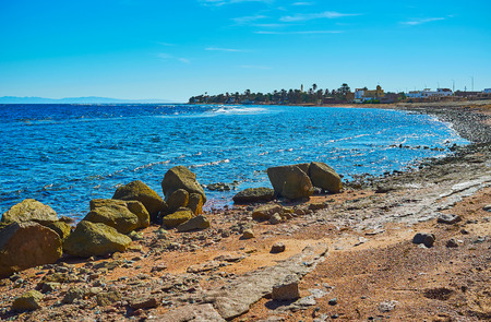 The rocky coastline of Aqaba gulf with boulders, protecting beach from the strong waves, Dahab, Sinai, Egypt. 写真素材