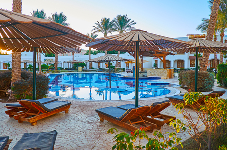 SHARM EL SHEIKH, EGYPT - DECEMBER 12, 2017: The cozy sun beds attract to relax at the pool and enjoy the scenic palm garden