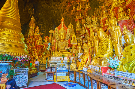 PINDAYA, MYANMAR - FEBRUARY 19, 2018:  Interior of Pindaya cave Buddhist site with a view on spectacular golden images of Lord Buddha and small stupa