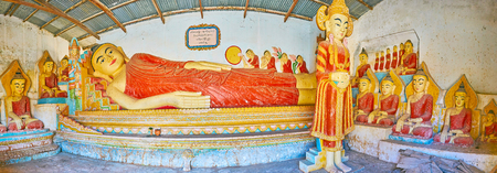 PINDAYA, MYANMAR - FEBRUARY 19, 2018: Panorama of the shrines interior with large Reclining Buddha, surrounded by smaller statues of Buddha in Earth Witness gesture, Kan Tu Kyaung monastery
