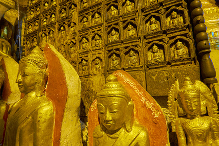 PINDAYA, MYANMAR - FEBRUARY 19, 2018: The gilded Buddha images with a view on carved teakwood Tataung decorated by multiple Buddha reliefs, in Pindaya cave Editorial