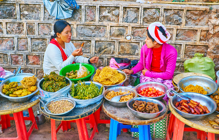 PINDAYA, MYANMAR - FEBRUARY 19, 2018: The food stalls at the Pindaya cave with wide range of traditional vegetable dishes, noodles and deep fried snacks 新聞圖片