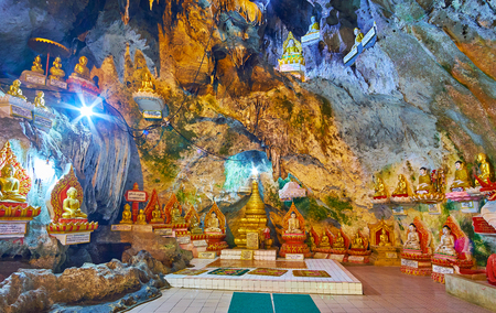 PINDAYA, MYANMAR - FEBRUARY 19, 2018: Tazaung (prayer hall) of the small stalactite cave of Pindaya complex with ornate golden stupa, Buddha images and Legendary fairy's loom post Editorial