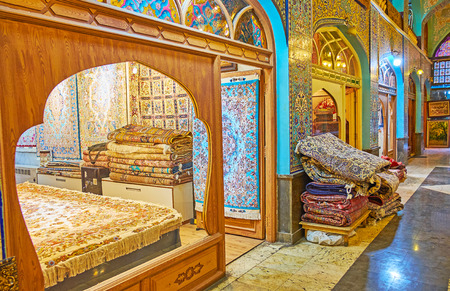 TEHRAN, IRAN - OCTOBER 10, 2017: Visit the scenic stores of covered Shah Abbasi carpet bazaar, famous for its luxury interior, decorated with tilework and carved details