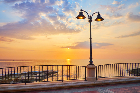 Watch the scenic cloudy sunrise from the central seaside promenade, stretching along the Sliema coast, Malta.