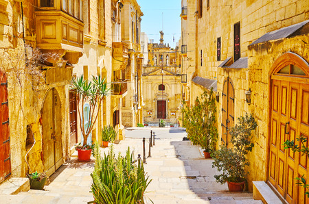 The medieval St Lucia street is decorated with green plants in pots; the same named church is seen at the end of the descent, Valletta, Malta. Stock Photo