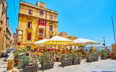 VALLETTA, MALTA - JUNE 19, 2018: The cozy outdoor terrace of the restaurant in St Ursula street of the old town, surrounded with plants in pots, on June 19 in Valletta Editorial