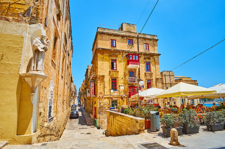 VALLETTA, MALTA - JUNE 19, 2018: St Ursula street is one of the medieval city streets with historical housing, outdoor cafes, wall statues and interesting tourist spots, on June 19 in Valletta