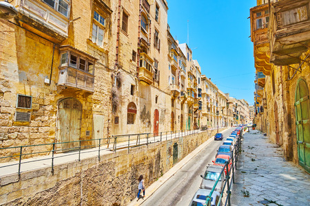 Walk the long stone Lvant street with a view on historical housing of limestone and typical wooden balconies, Valletta, Malta. 免版税图像 - 120987806