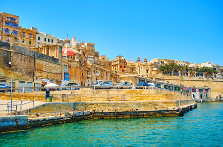 The coast of Valletta with preserved medieval ramparts, red dome of Liesse church and old townhouses in upper city, Malta.