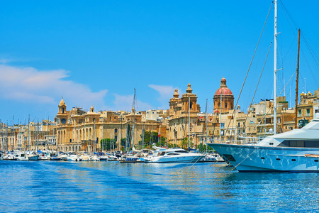 The skyline of Birgu with sails of yachts, clock tower of Maritime museum and dome with bell towers of St Lawrence church, Malta.