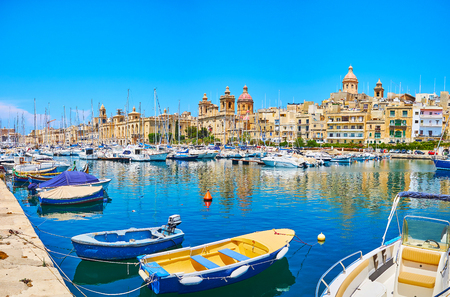 SENGLEA, MALTA - JUNE 19, 2018: L-Isla seaside promenade faces Vittoriosa marina with yachts, fishing boats and Birgu fortified city on the opposite shore, on June 19 in Senglea.