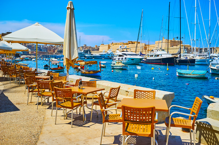 The cozy outdoor seaside restaurant in Senglea offers picturesque view on Vittoriosa marina and Birgu's Fort St Angelo on background, Malta.