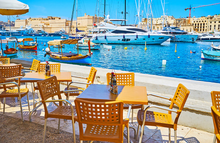 Relax in outdoor lounge cafe, located on the shore of Senglea and overlooking Vittoriosa Marina and medieval Birgu, Malta. Фото со стока