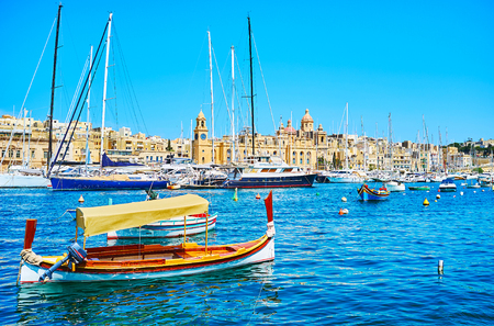 The lonely luzzu boat in front of the moored yachts in Vittoriosa marina and medieval Birgu on the opposite shore, Malta. Banco de Imagens