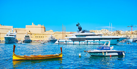 Senglea seaside promenade is the nice place to overlook Vittoriosa port with a view on splendid modern yachts at the shore of Birgu and traditional wooden luzzu boats on the foreground, Malta. Banco de Imagens