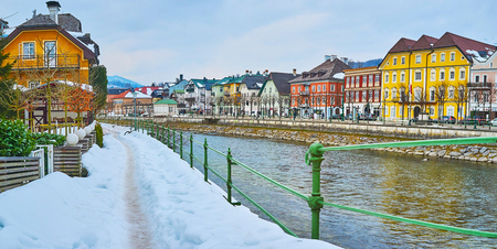 The snowy riverside cityscape of Bad Ischl - the famous spa resort of Salzkammergut with preserved historical architecture, Austria.