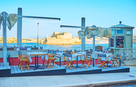 The small outdoor cafe in Briiera Wharf overlooks the Great Harbour of Valletta and Fort Sta Angelo of Birgu, Malta