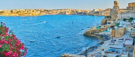 Panorama of the picturesque Grand Harbour with a view on Kalkara city, Fort St Angelo of Birgu, Siege Bell War Memorial, St Christopher bastion and small fishermen's huts along Valletta shore, Malta