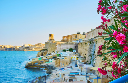 Enjoy the evening on Valletta shore with a view on the medieval ramparts, Siege Bell War Memorial, small fishing houses and blooming bush, Malta