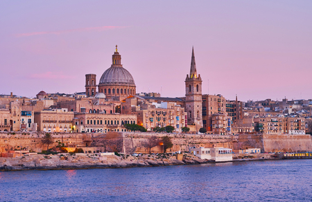 The medieval limestone city looks great in purple sunset colors, the beautiful Valletta skyline with its main symbols - bell tower of St Paul Pro-Cathedral and large dome of Carmelite church, Malta