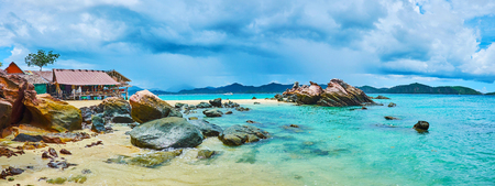 Panorama of idyllic coastline of Khai Nai island with clear white sand, giant boulders and mountain landscape behind emerald waters of Andaman sea, Phuket, Thailand