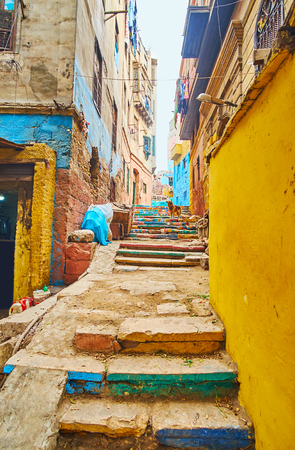 The narrow hilly backstreet in shabby neighborhood with colorful stairs and line of old residential houses, Cairo, Egypt Stock Photo