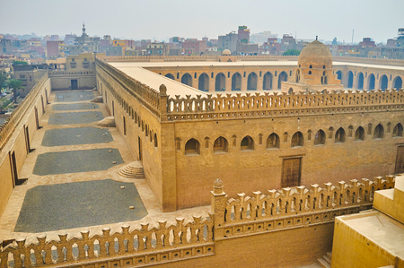 The outer and inner walls of medieval Ibn Tulun mosque, decorated with carved battlements and arched windows; the dome of ablution fountain is seen amid the court, Cairo, Egypt