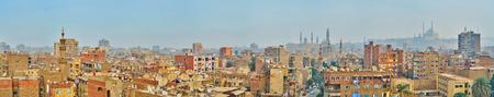 Panorama con los techos de los edificios vivientes del distrito de Al-Sayeda Zeinab, los minaretes de las mezquitas brumosas y la ciudadela de El Cairo en el fondo, Egipto