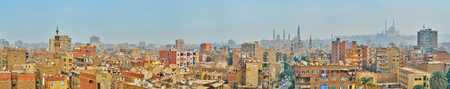 Panorama with living buildings' roofs of Al-Sayeda Zeinab district, hazy mosques' minarets and Cairo Citadel on the background, Egypt