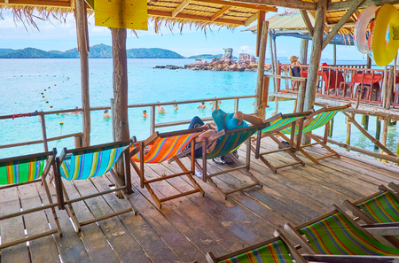 PHUKET, THAILAND - MAY 1, 2019: The wooden terrace in shady hut on stilts with sun beds for the holidaymakers, relaxing on the Khai Nai island, on May 1 on Phuket 新聞圖片