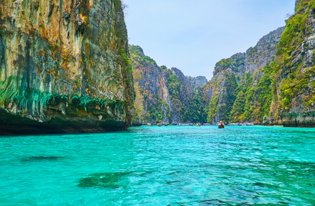 The bright emerald waters of Pileh Bay lagoon, surrounded by huge cliffs of Phi Phi Leh Island, Krabi, Thailand