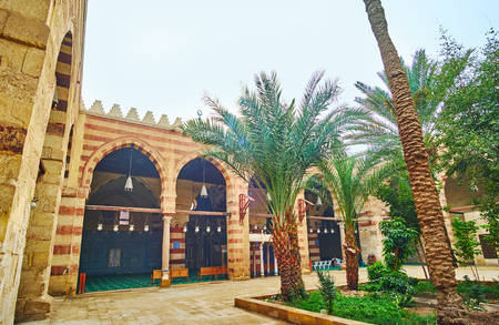 CAIRO, EGYPT - DECEMBER 22, 2017: The view on arcade of Aqsunqur (Blue) Mosque through the lush greenery of its garden, on December 22 in Cairo