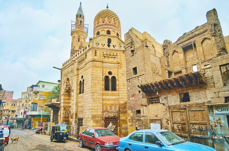CAIRO, EGYPT - DECEMBER 22, 2017: The scenic medieval mosque of Prince Aytmish El Bagassi with carved zigzag dome and muqarnas arch, located in alley of Al Wazir street in Islamic Cairo district, on December 22 in Cairo