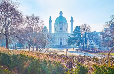 The morning walk along small cozy Resselpark in central Vienna with bare trees, playground and huge Karlskirche on the background, Austria