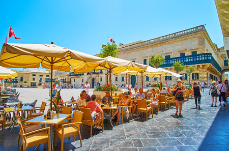 VALLETTA, MALTA - JUNE 19, 2018: Relax in nice outdoor restaurant of Old Theatre street, located next to the St George square and Grand Masters Palace, seen on background, on June 19 in Valletta Editorial