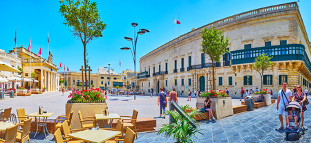 VALLETTA, MALTA - JUNE 19, 2018: Panorama of St George square with a view on Grand Masters Palace, and portico of Chancellery building behind the flower beds of Old Theatre street, on June 19 in Valletta Editorial
