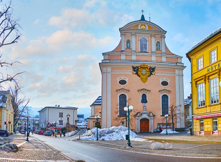 BAD ISCHL, AUSTRIA - FEBRUARY 20, 2019: The modest facade of St Nicholas Parish Church, decorated with relief coat of arms, faces Franz Joseph Strasse, on February 20 in Bad Ischl
