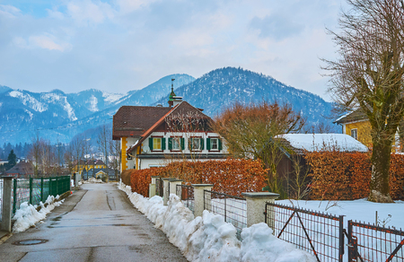 The quiet winter street with line of scenic houses, small gardens and foggy Alps on background, Bad Ischl, Salzkammergut, Austria.