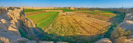 Panorama of farm lands, surrounded by medieval adobe rampart of Ghaleh Jalali citadel with a view on preserved yakhchals - ancient evaporative coolers, shaped as pyramids, Kashan, Iran.