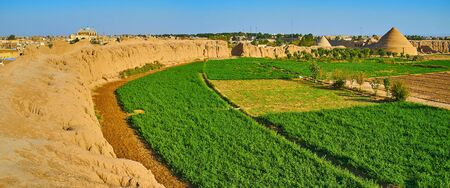 The ruins of adobe Ghaleh Jalali citadel with agricultural lands inside of ramparts and yakhchal pyramids - ancient evaporative coolers on background, Kashan, Iran.