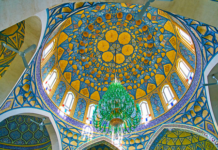 ARAN-O-BIDGOL, IRAN - OCTOBER 23, 2017: Turquoise gamma tile cupola of Imamzadeh Helal Ali Holy Shrine with carved honeycomb (muqarnas) decoration, arabesques, Quranic calligraphy and vintage glass chndelier, on October 23 in Aran-o-Bidgol Editorial