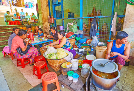 POPA, MYANMAR - FEBRUARY 26, 2018: The food sellers offer tasty dishes of Burmese cuisine in market of Taung Kalat Temple, pilgrims have lunch at small tables in hall of market, on February 26 in Popa