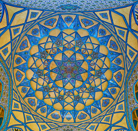 ARAN-O-BIDGOL, IRAN - OCTOBER 23, 2017: The dome in portal of Imamzadeh Helal Ali Holy Shrine is fdecorated with muqarnas carving and tile arabesques in turquoise gamma, on October 23 in Aran-o-Bidgol